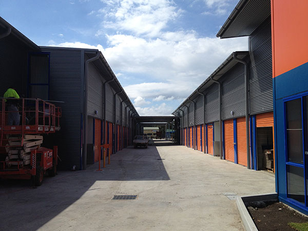 Commercial roofing project at Kennards Self Storage Wollongong showing new Zincalume roofs, wall cladding, downpipes, gutters, trims and flashings in specialty metallic finishes.